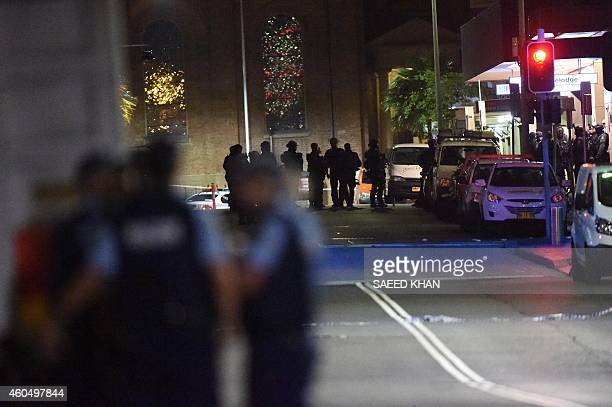Armed police carry out an operation outside the cafe where a gunman had taken people captive in the central business district of Sydney on December...