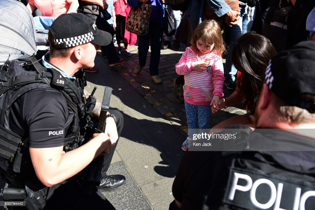 Armed police officers crouch down to chat to a young girl on the Royal Mile during the Edinburgh Festival Fringe where security has this year been stepped up, on August 17, 2017 in Edinburgh, Scotland. The Fringe is celebrating its 70th year, and this year hosts over three thousand shows and more than 50,000 performances.