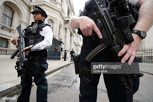 Armed police officers hold guns as they stand in Downing Street in central London on August 29 2014 British Home Secretary Theresa May said on August...