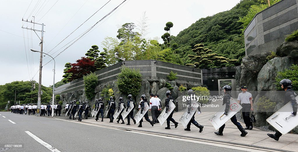 Armed police officers leave the headquarters of Japanese yakuza organization Kudokai after a raid on June 6, 2014 in Kitakyushu, Fukuoka, Japan. The police raided the gang group on suspicion of involvement of the stabbing a dentist.
