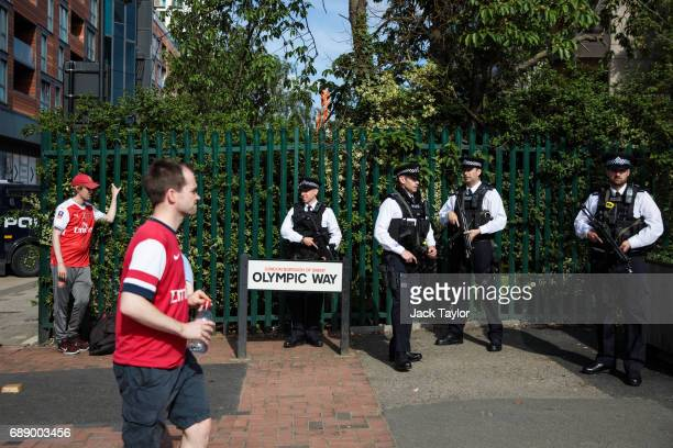 Armed police officers look on as football fans make their way to Wembley Stadium ahead of the FA Cup final on May 27 2017 in London England Football...