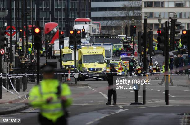 Armed police officers man a security cordon as members of the emergency services work on Westminster Bridge alonside the Houses of Parliament in...