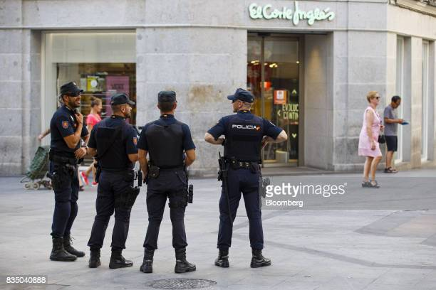 Armed police officers patrol a pedestrian shopping area outside the El Corte Ingles SA department store on Preciados street in Madrid Spain on Friday...