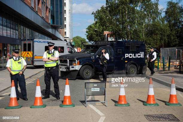 Armed police officers patrol as football fans make their way to Wembley Stadium ahead of the FA Cup final on May 27 2017 in London England Football...