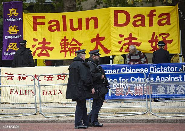 Armed police officers patrol in front of antiChinese government protesters positioned on the Mall in central London on October 20 2015 for the...