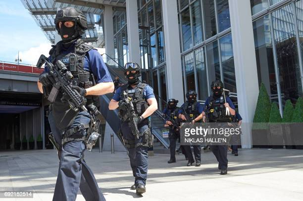 Armed police officers patrol outside The Shard tower and London Bridge railway station in London on June 4 as police continue their investigations...