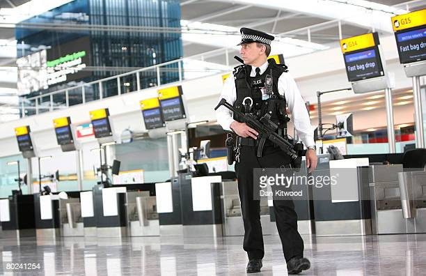 Armed police officers patrol the new Terminal 5 at Heathrow Airport prior to its official opening on March 14 2008 in London England Following...