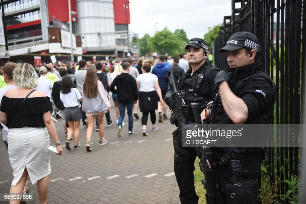 Armed police officers secure the area as revellers arrive to attend the Courteeners concert at Old Trafford cricket ground in Manchester northwest...