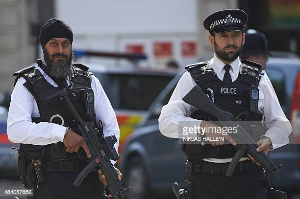 Armed police officers stand guard ahead of a Service of Commemoration at St MartinintheFields church in central London on August 15 to mark the 70th...