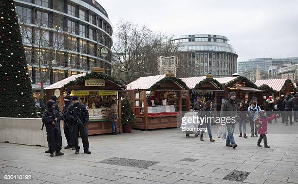 Armed police officers stand guard beside festive stalls as Berlin Christmas market reopens in Berlin Germany on Thursday Dec 22 2016 German...
