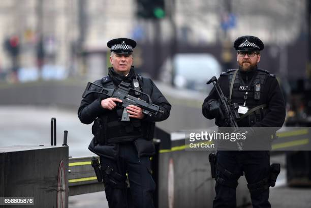 Armed police officers stand guard near Parliament following yesterday's attack on March 23 2017 in London England Four people including the assailant...