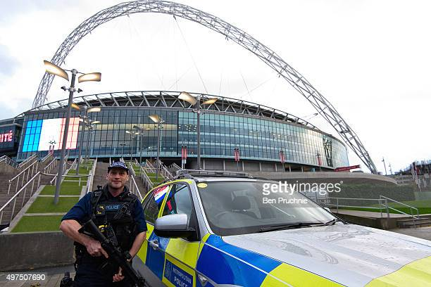 Armed police officers stand guard outside Wembley Stadium ahead of tonight's football match between England and France on November 17 2015 in London...