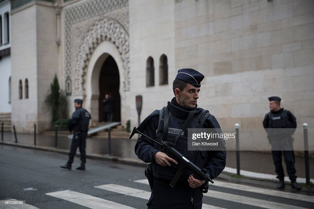 Armed police officers stand outside the Grand Mosque on January 9 2015 in Paris France A huge manhunt for the two suspected gunmen in Wednesday's...