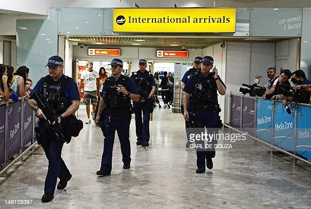 Armed police officers walk in front of the arrival gate at Heathrow airport London on July 23 four days ahead of the London 2012 Olympic Games AFP...