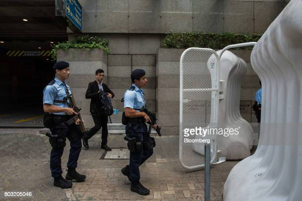 Armed police officers walk past water barricades near the Hong Kong Convention and Exhibition Center ahead of the 20th anniversary of Hong Kong's...