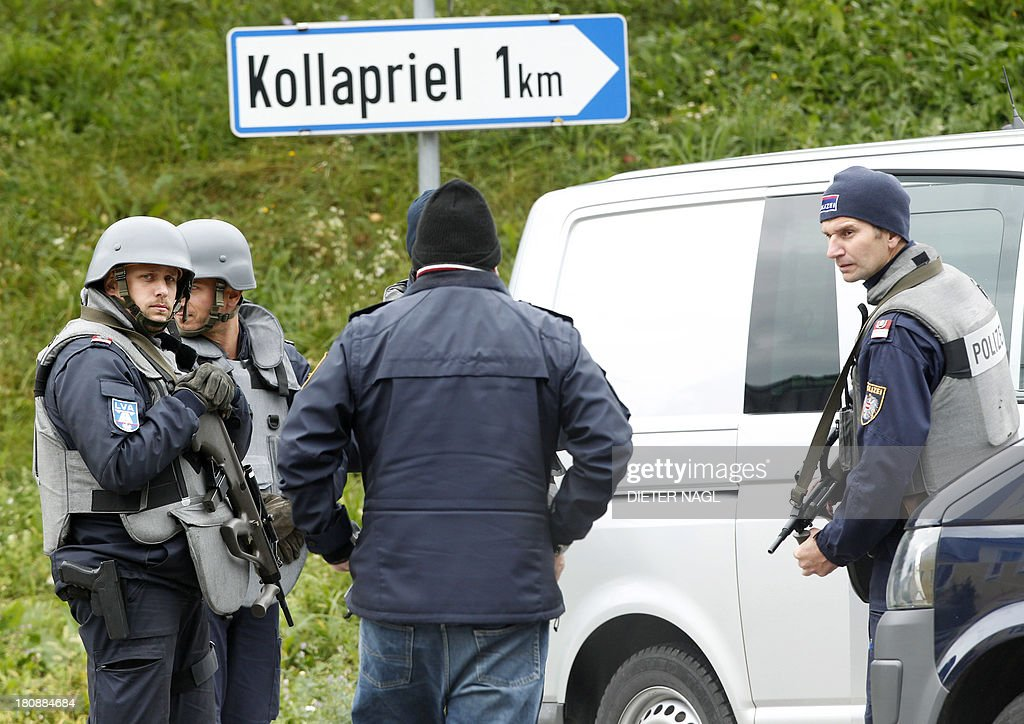 Armed police officiers block a road near Grosspriel, some 65 kilometers west of Vienna, on September 17, 2013 where a man hides himself with a police officers as hostage in a farmhouse, after he allegedly shot dead a paramedic and three policemen. The man was holed up in his house at Grosspriel near Melk, some 90 kilometres (55 miles) west of Vienna, police spokesman Johann Baumschlager said.