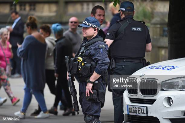 Armed police patrol Albert Square as members of the public lay floral tributes and messages on May 24 2017 in Manchester England An explosion...