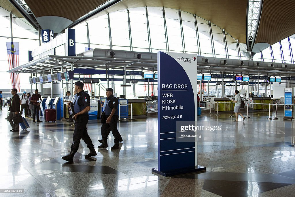 Armed police patrol near the Malaysian Airline System Bhd. (MAS) check-in counter at Kuala Lumpur International Airport (KLIA) in Sepang, Malaysia, on Tuesday, Aug. 26, 2014. Malaysia Airlines are scheduled to release second quarter earnings Aug. 27 as the airline considers job cuts, a review of aircraft orders and replacing its chief executive officer after the national carrier suffered two disasters this year, people familiar with the plan said. Photographer: Charles Pertwee/Bloomberg via Getty Images