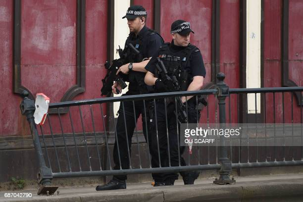 Armed police patrol near Victoria station in Manchester northwest England on May 23 2017 Twenty two people have been killed and dozens injured in...