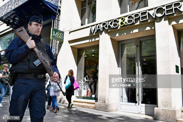 Armed police patrol past the Marks Spencer on the Champs Elysees in Paris following yesterday's shooting of a police officer on April 21 2017 in...