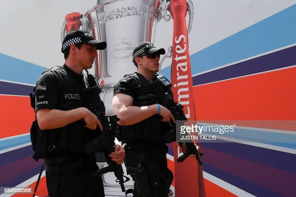 Armed police patrol the way toward Wembley Stadium in London on May 27 2017 ahead of the English FA Cup final football match between Arsenal and...