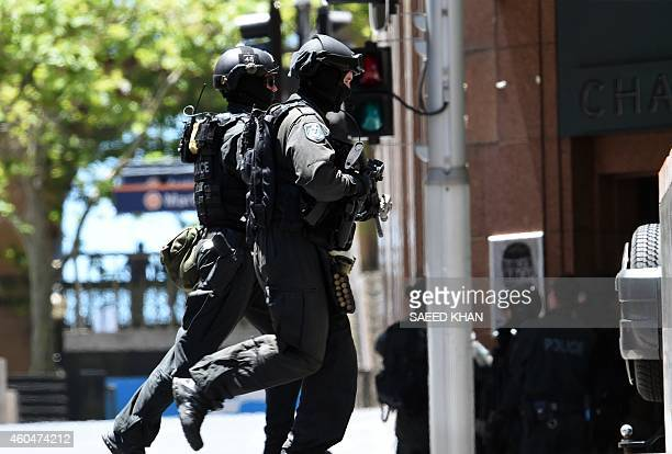 Armed police run toward a cafe in the central business district of Sydney on December 15 2014 Hostages were being held inside a cafe in central...