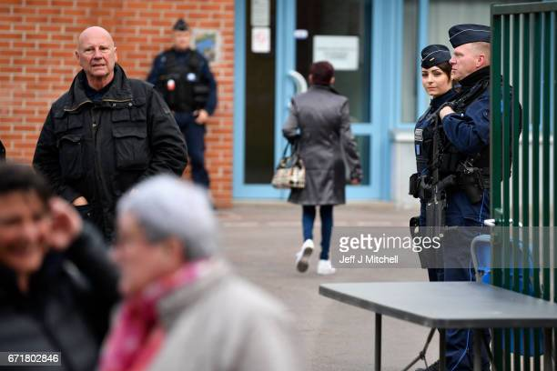 Armed police stand guard at a polling station as voting gets underway for the French elections on April 23 2017 in Henin Beaumont France French...