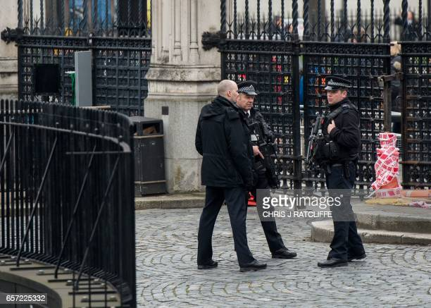 Armed police stand guard at the entrance to the Houses of Parliament which remain closed in central London on March 24 2017 two days after the March...