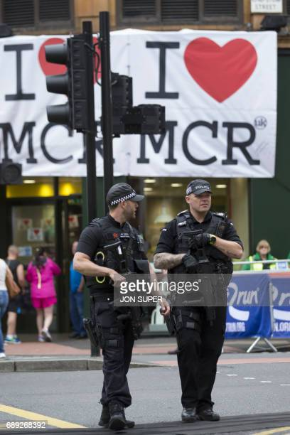 Armed police stand guard at the start of the Great Manchester Run in Manchester on May 28 2017 Britain police have released CCTV footage of...