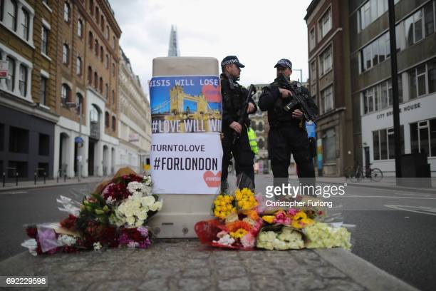 Armed police stand guard in front of floral tributes on Southwark Street near the scene of last night's terrorist attack on June 4 2017 in London...