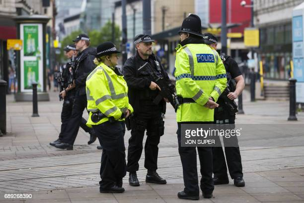 Armed police stand guard near the start of the Great Manchester Run in Manchester on May 28 2017 Britain police have released CCTV footage of...