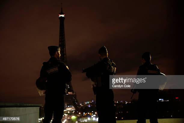 Armed police stand guard overlooking the Eiffel Tower which was kept dark in honor of those who died in the terrorist attacks yesterday November 14...
