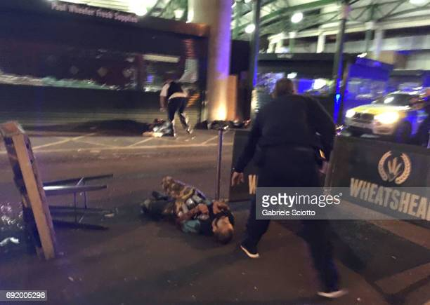 TOPSHOT Armed police stand over what is believed to be a suspect shot at the scene of a terror attack outside Borough Market in central London on...