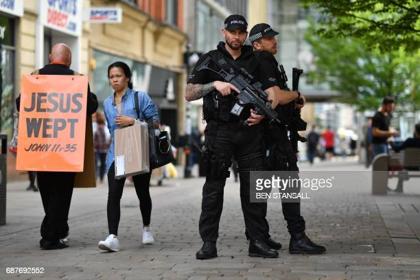 Armed police stand secure a street in central Manchester northwest England on May 24 following the May 22 terror attack at the Manchester Arena...