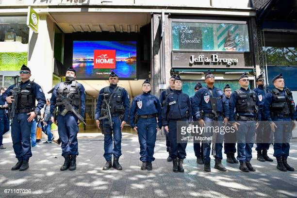 Armed police stand to attention near where their fallen colleague was shot on the Champs Elysees yesterday on April 21 2017 in Paris France One...
