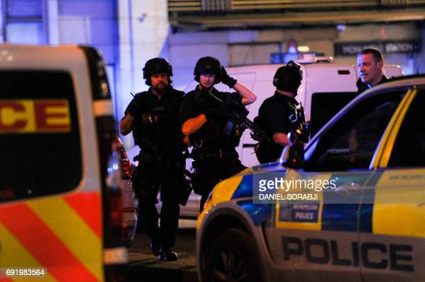 Armed police take position at the scene of a terror attack on London Bridge in central London on June 3 2017 Armed police fired shots after reports...