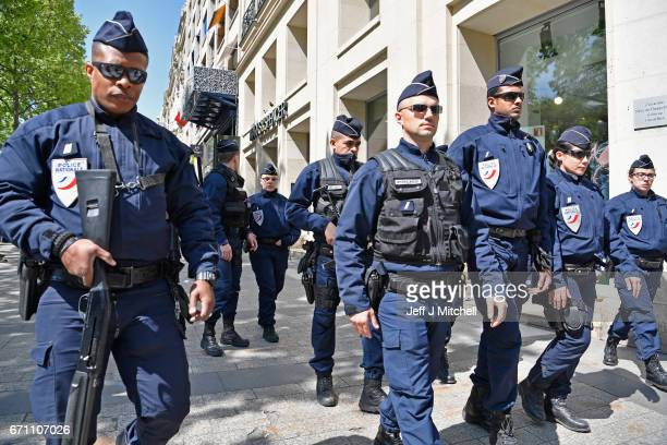Armed police walk past Marks Spencer where their fallen colleague was shot yesterday on the Champs Elysees on April 21 2017 in Paris France One...