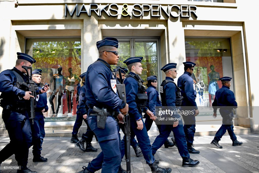 Armed police walk past Marks & Spencer where their fallen colleague was shot yesterday on the Champs Elysees on April 21 2017 in Paris, France. One police officer was killed and another wounded in a shooting on Paris's Champs Elysees, police said just days ahead of France's presidential election. France's interior ministry said the attacker was killed in the incident on the world famous boulevard that is popular with tourists.