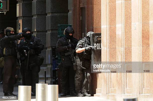 Armed policeman are seen outside Lindt Cafe on Philip St Martin Place on December 15 2014 in Sydney Australia Police attend a hostage situation at...