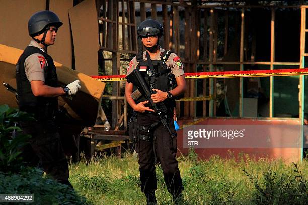 Armed policemen secure a bomb damaged wooden structure following an explosion in Jakarta on April 8 2015 The explosion in the densely populated area...