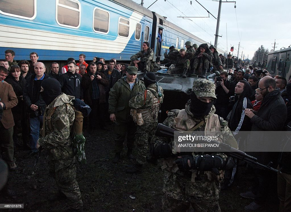 Armed pro-Russia activists block a column of Ukrainian soldiers riding on Armoured Personnel Carriers in the eastern Ukrainian city of Kramatorsk on April 16, 2014. Ukraine's security service said on April 16 it had intercepted communications showing that Russian commanders in the separatist east had issued pro-Kremlin militants 'shoot-to-kill' orders after Kiev launched an operation to oust them.
