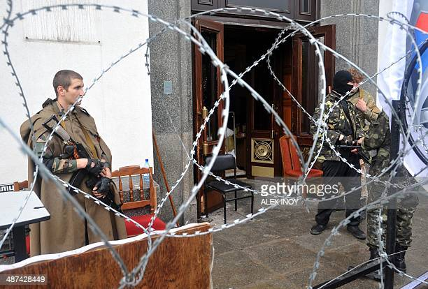 Armed proRussian militants stand guard outside the regional state building seized by separatists in the eastern Ukrainian city of Lugansk on April 30...