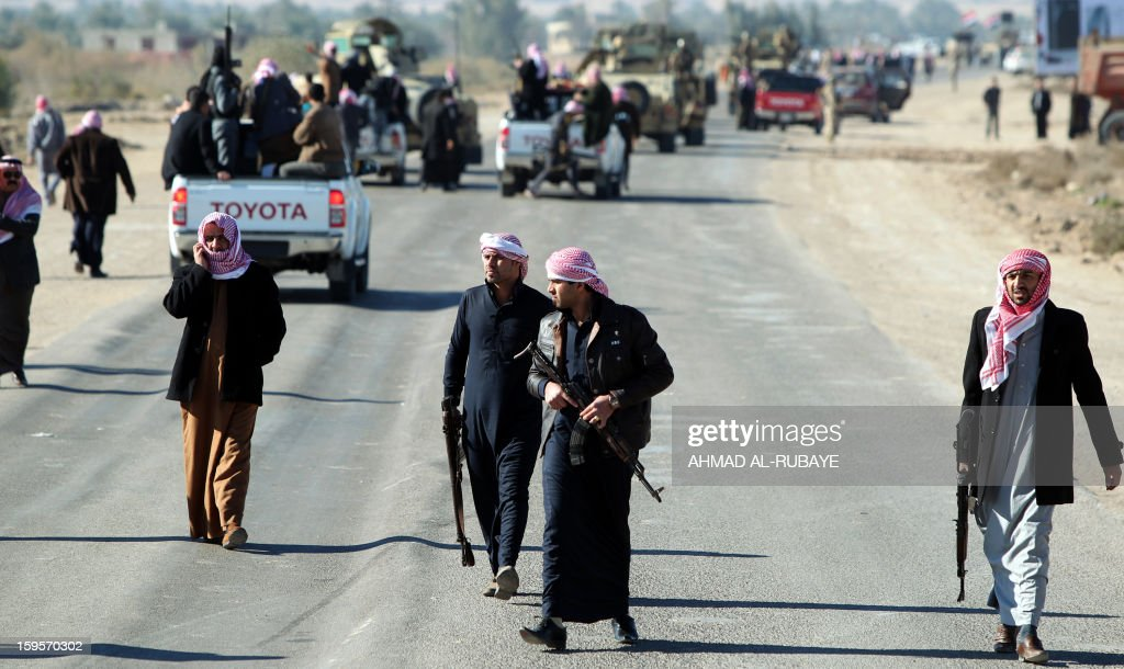 Armed relatives and tribe members protect the road during the funeral procession of MP Ayfan Saadun al-Essawi, of the secular Sunni-backed Iraqiya bloc, in the western town of Fallujah, 50 kilometers from Baghdad, on January 16, 2013, in Anbar province. Essawi, 37-years-old, was killed by a suicide bomber who wrapped his arms around the lawmaker before blowing himself up, as a political crisis engulfed Iraq.