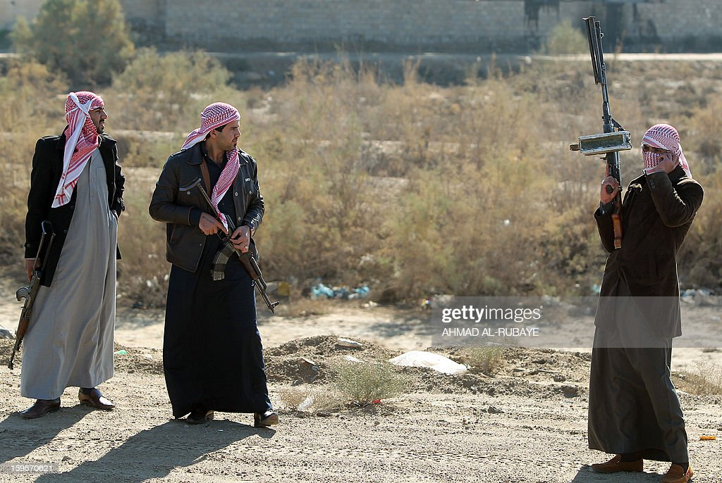 Armed relatives and tribe members protect the road during the funeral procession of MP Ayfan Saadun al-Essawi, of the secular Sunni-backed Iraqiya bloc, in the western town of Fallujah, 50 kilometers from Baghdad, on January 16, 2013, in Anbar province. Essawi, 37-years-old, was killed by a suicide bomber who wrapped his arms around the lawmaker before blowing himself up, as a political crisis engulfed Iraq. AFP PHOTO/AHMAD AL-RUBAYE