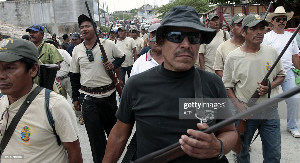 Armed residents --community police-- take part in the March for Justice and Dignity, in Ayutla de los Libres, on March 2, 2013, in the southwestern State of Guerrero, Mexico. Hundreds of civilians armed with rifles, pistols and machetes decided to provide security for the communities of Guerrero, creating a vigilante force, saying gangs were committing robberies, kidnappings and murder. Guerrero, home to the Pacific resort town of Acapulco, has been one of the states hardest hit by Mexico's drug violence, which has left more than 70,000 people killed across the country since 2006. AFP PHOTO/Pedro Pardo