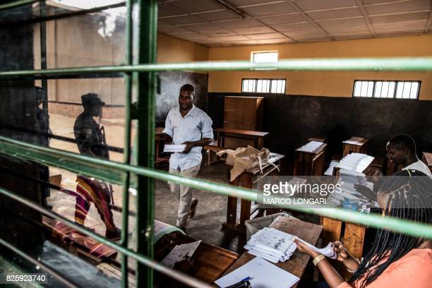 Armed Rwandan police officers are reflected in the window of a polling station where election officials set up ballot papers on August 3 2017 in...