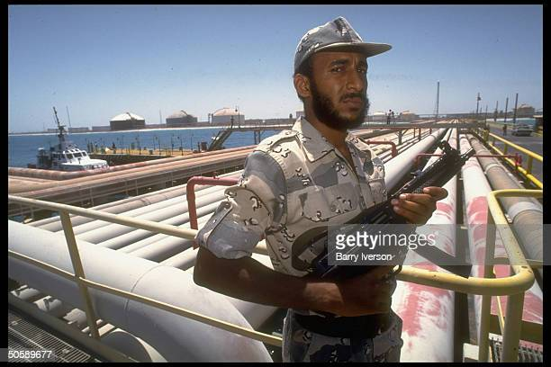 Armed security guard poised by pipelines port facilties at Saudi Aramco oil refinery loading terminal at Ras Tanura Saudi Arabia