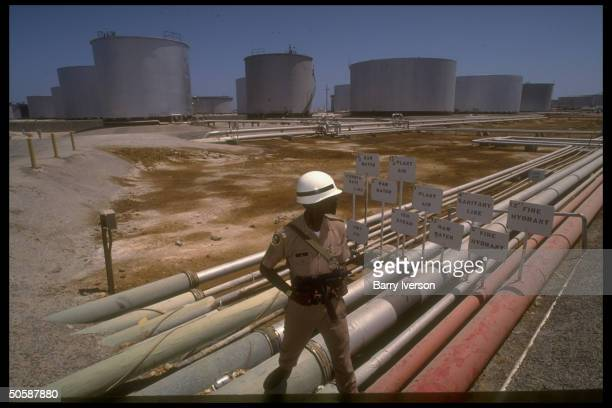 Armed security guard poised by pipelines storage tanks at Saudi Aramco oil refinery loading terminal at Ras Tanura Saudi Arabia