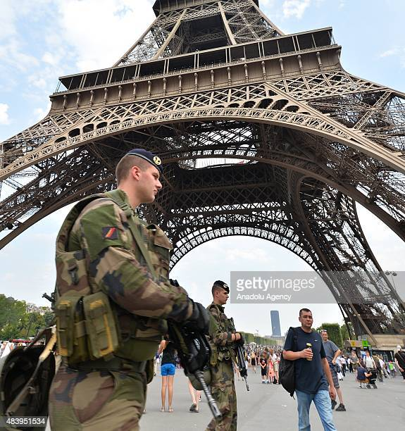 Armed soldiers patrol around the Eiffel Tower in Paris France on August 14 2015