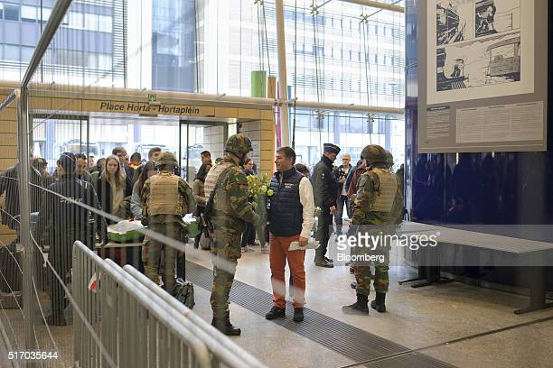 Armed soldiers stand guard and check travelers baggage as they enter Brussels Midi railway station in Brussels Belgium on Wednesday March 23 2016...